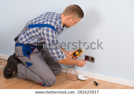Male Electrician Checking Voltage Of Socket With Multimeter In House - stock photo