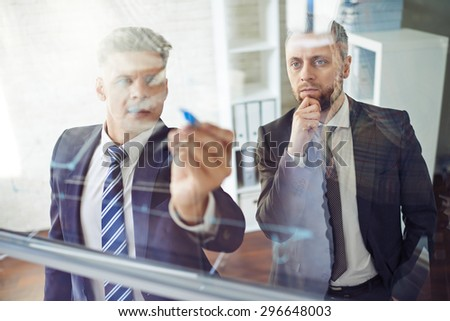 Male employee explaining graph on transparent board - stock photo