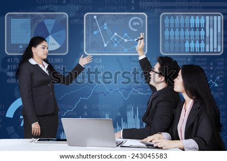 Male employee raising hand and inquiring on his manager when meeting together in the office - stock photo