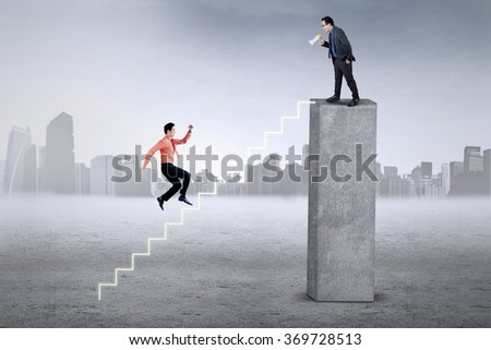 Male employee running hurry on the stair to meet with his boss on the top - stock photo