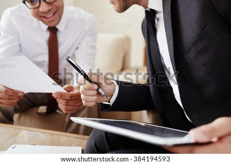 Male employee with digital tablet and pen communicating with colleague at meeting - stock photo