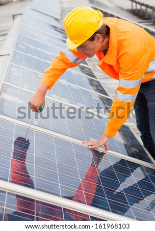 Male Engineer Adjusting Solar Panels With Work Tool - stock photo