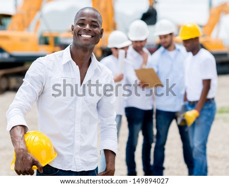Male engineer at the construction site looking very happy  - stock photo