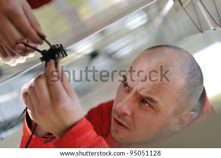 Male engineer at work place, solar panels plant industry in background - stock photo