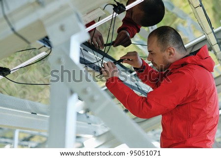 Male engineer at work place, solar panels plant industy in background - stock photo