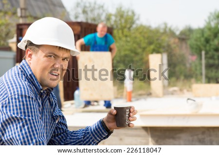 Male Engineer Holding Cup of Coffee While Looking at the Camera at Project Site. - stock photo
