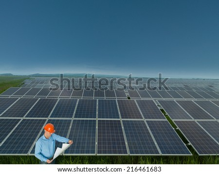 male engineer standing and reading blueprints in solar power station - stock photo