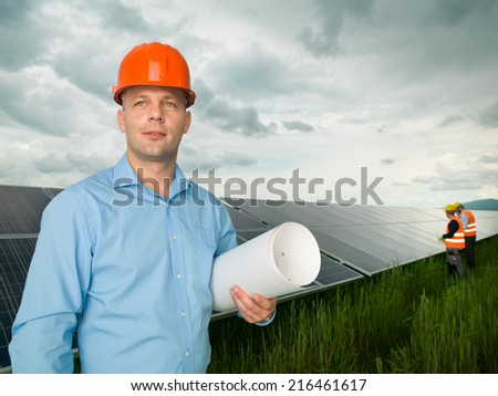 male engineer standing in solar panel station, holding blueprints, with two other workers in background - stock photo
