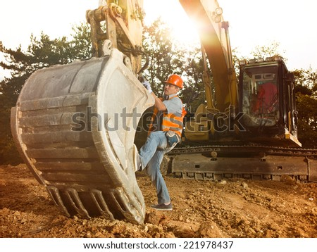 male engineer standing next to excavator on construction site outdoors, with sunlight in background - stock photo