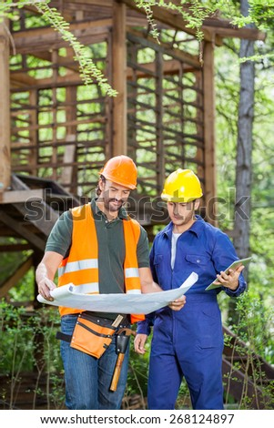 Male engineers with digital tablet analyzing blueprint outside wooden cabin at construction site - stock photo
