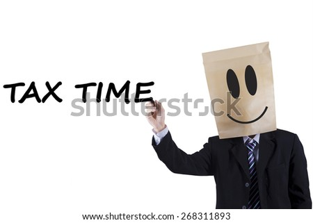 Male entrepreneur with a cardboard head writes tax time on whiteboard to remind the time for paying tax - stock photo