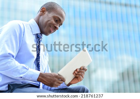 Male executive looking digital tablet at outdoors - stock photo
