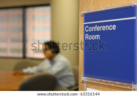 Male executive using phone in conference room - stock photo
