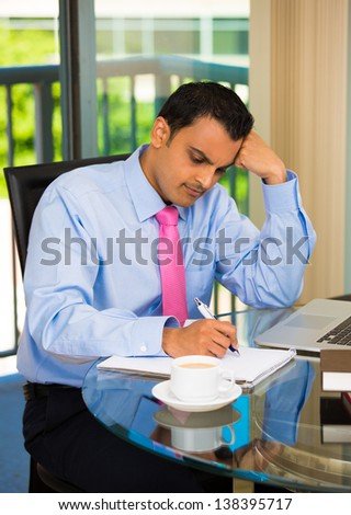 Male executive working hard on laptop computer, making notes at office - stock photo