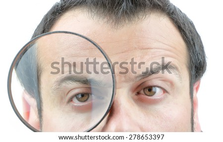 Male face looking in the magnifying glass - stock photo