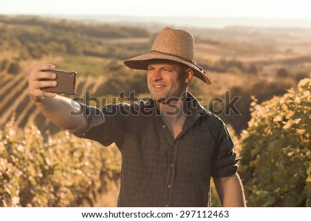 Male farmer in his vineyard making selfie picture - stock photo