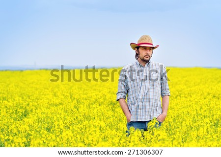 Male Farmer Standing in Oilseed Rapeseed Cultivated Agricultural Field Examining and Controlling The Growth of Plants, Crop Protection Agrotech Concept. - stock photo