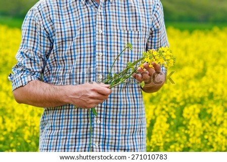 Male Farmer Standing in Oilseed Rapeseed Cultivated Agricultural Field Holding Canola Flowers for Examining and Controlling The Growth of Plants, Crop Protection Agrotech Concept. - stock photo