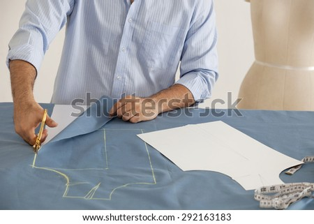 Male fashion designer working in fashion studio - stock photo