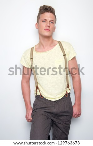Male fashion model posing with suspenders - stock photo
