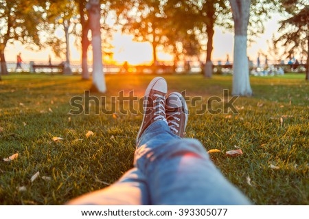 Male feet in gumshoes on green grass in the park at sunset - stock photo