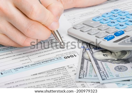 Male filling out 1040 United States of America Tax Form - stock photo