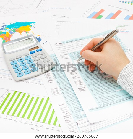 Male filling out 1040 US Tax Form with ball pen - studio shot - stock photo