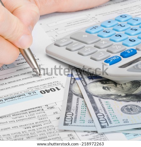 Male filling out 1040 US Tax Form with calculator and money on table - 1 to 1 ratio - stock photo