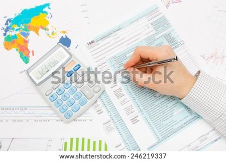 Male filling out 1040 US Tax Form with silver pen - stock photo