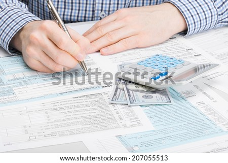 Male filling out 1040 USA Tax Form - studio shot - stock photo