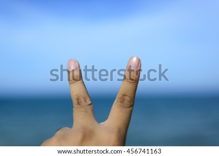 Male fingers showing number isolated on bokeh blue-sea background. Copyspace is available. - stock photo