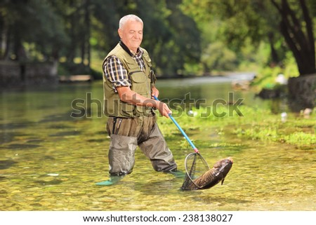 Male fisherman catching fish with net in a river on a sunny summer day  - stock photo