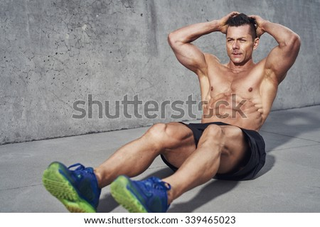 Male fitness model doing sit ups and crunches exercising abdominal muscles, six pack visible wearing no shirt - stock photo
