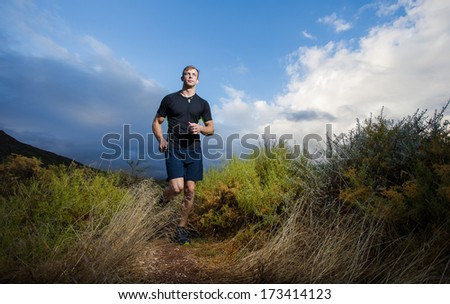 Male fitness model running allong a trail in the field, wearing a black shirt and shorts, with big clouds ooverhead in the sky. - stock photo