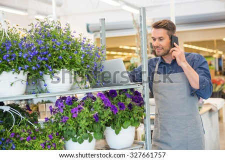 Male florist using mobile phone and laptop in flower shop - stock photo