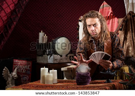 Male fortune teller with tarot cards waving hand over crystal ball - stock photo