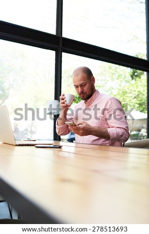 Male freelancer connecting to wireless on his smart phone during coffee break, modern business man typing text message oh cell phone while working in loft studio, university student working at cafe - stock photo