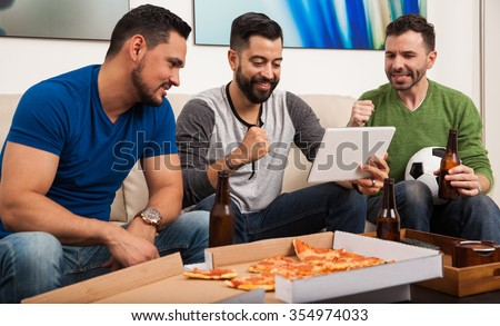 Male friends drinking beer and eating pizza while watching a soccer game on a tablet computer - stock photo
