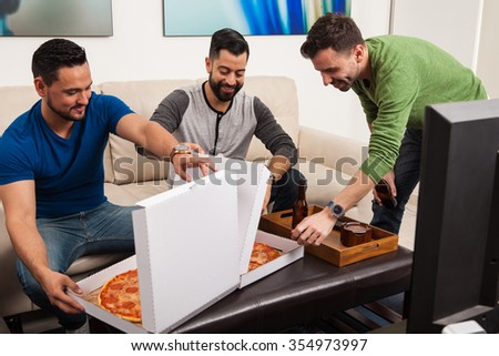 Male friends hanging out at home and watching a game on tv while enjoying some pizza - stock photo