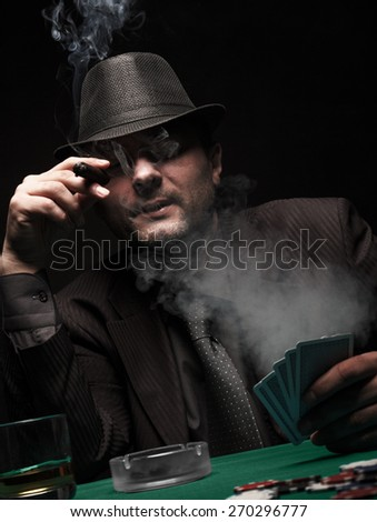 Male gambler playing poker and smokes a cigar, Dark color Intensity. - stock photo