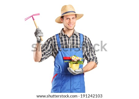 Male gardener holding flower plant and a mattock isolated on white background - stock photo