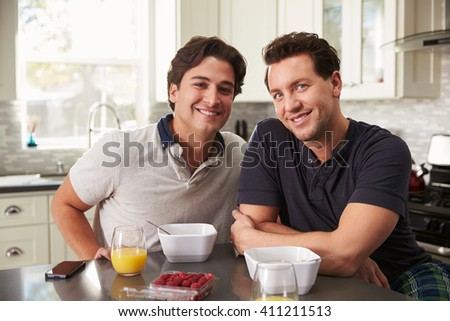 Male gay couple having breakfast in kitchen look to camera - stock photo
