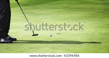 Male golf player in black with shadow putting on green with ball rolling towards hole, with plenty of copy-space. - stock photo