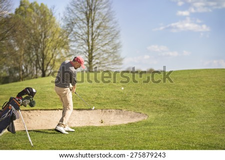 Male golf player pitching ball in front of bunker, with golf bag aside. - stock photo