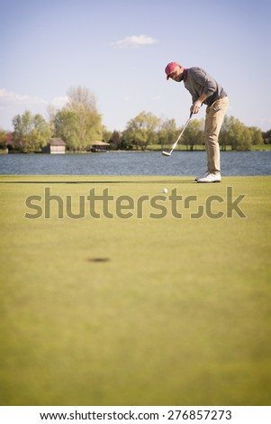Male golf player putting with golf club on green, with lake in background and blank copyspace. - stock photo