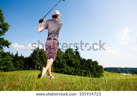 Male golf player teeing off golf ball from tee box with clean blue sky background - stock photo