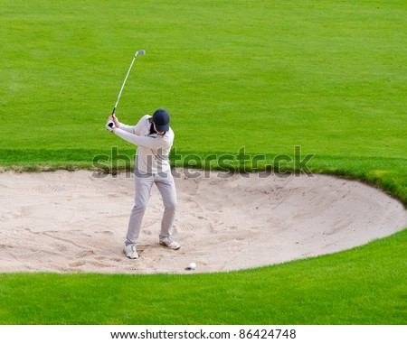 male golfer about to hit out of a sand bunker - stock photo