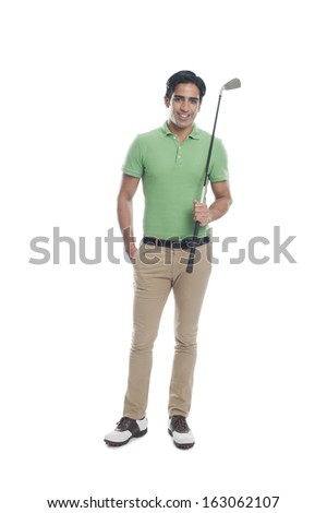 Male golfer holding a golf club and smiling - stock photo