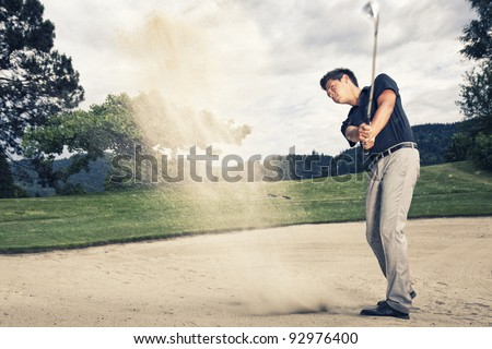 Male golfer in blue shirt and grey pants hitting golf ball out of a sand trap with sand wedge and sand caught in motion. - stock photo