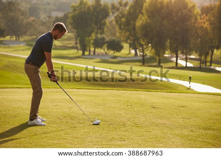 Male Golfer Lining Up Tee Shot On Golf Course - stock photo